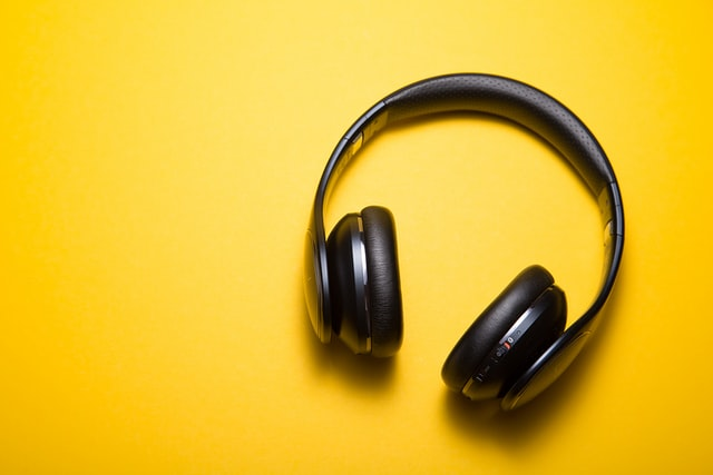 Black over-ear headphones on a bright yellow background.