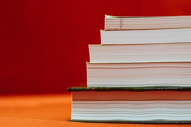 Stack of books with pages facing screen, with a dark orange background.